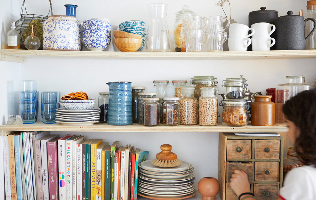 Kitchenware, books and jars of dry ingredients on three wooden shelves.