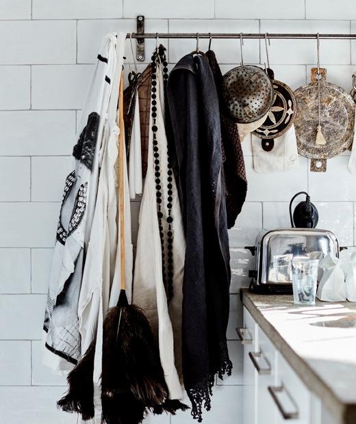 Kain, lap dan saringan tergantung di rel logam di dinding ubin putih.