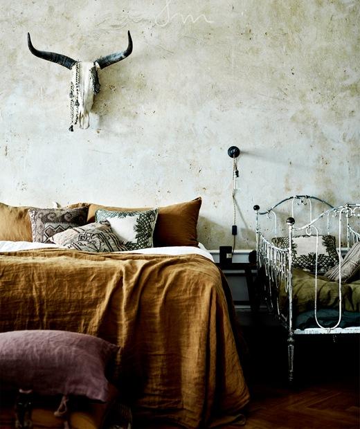 Sebuah tempt tidur dengan seprai warna tembaga di sebelah tempat tidur bayi berbahan logam putih, dengan tengkorak binatang di dinding bagian atas.