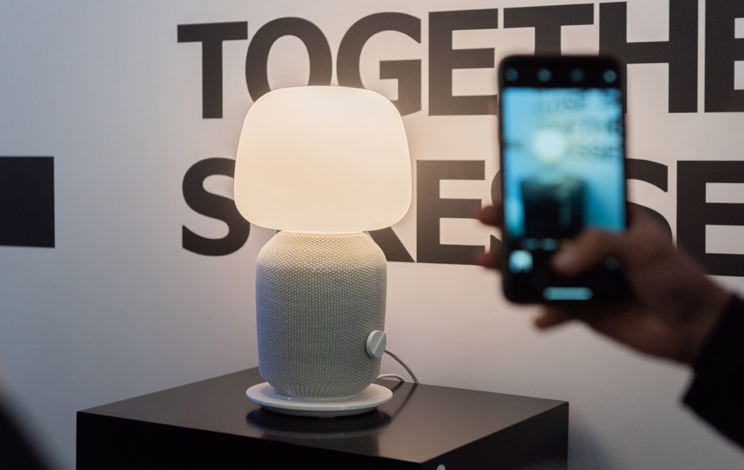 A new SYMFONISK speaker shaped like a table lamp sits on a stand and is photographed against a graphic sign.