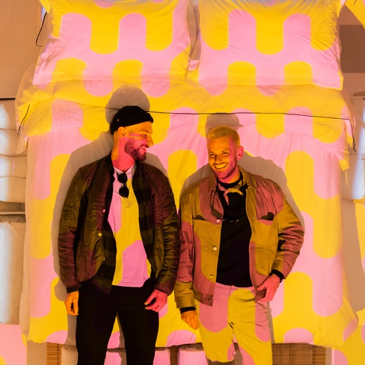 Two people stand in front of an image of a bed with pink and yellow bedding.