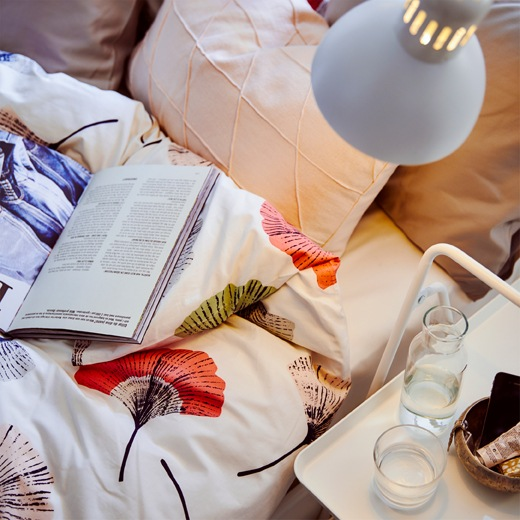 A lamp shines on floral bedding, pillows and a book, and a glass of water and carafe on a small white side table.