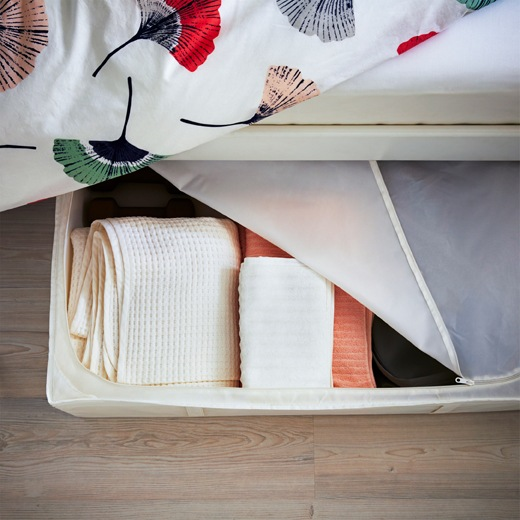 Towels stored in a zip-cover box under the side of a bed with floral bedding.