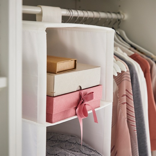Cardboard boxes stacked inside a hanging organiser next to clothes on a rail.