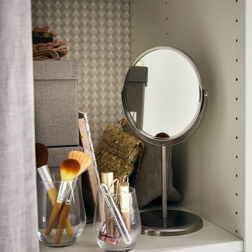 A small mirror and pots of make-up supplies on a shelf with storage boxes.