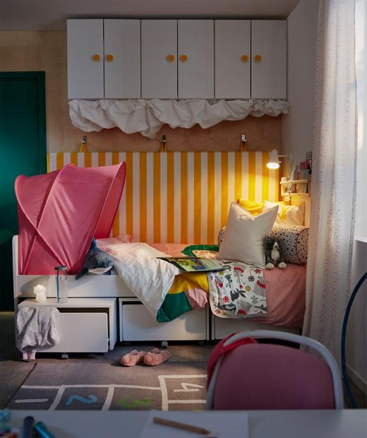 Pojok tempat tidur dari kamar anak, ranjang memiliki kasur yang tergantung di dinding di belakangnya, penyimpanan ada di bawah dan atas.