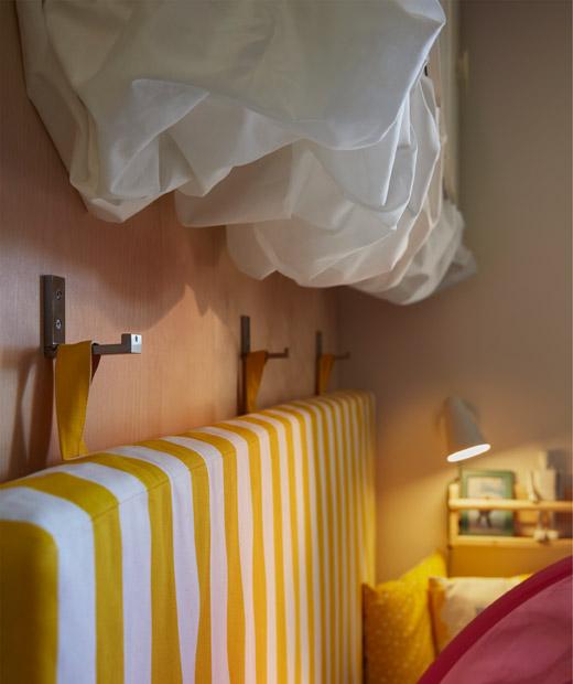 Sebuah kasur tergantung pada pengait dinding di samping tempat tidur. Kain warna putih dipasang di bawah lemari dinding sebagai hiasan berbentuk awan.