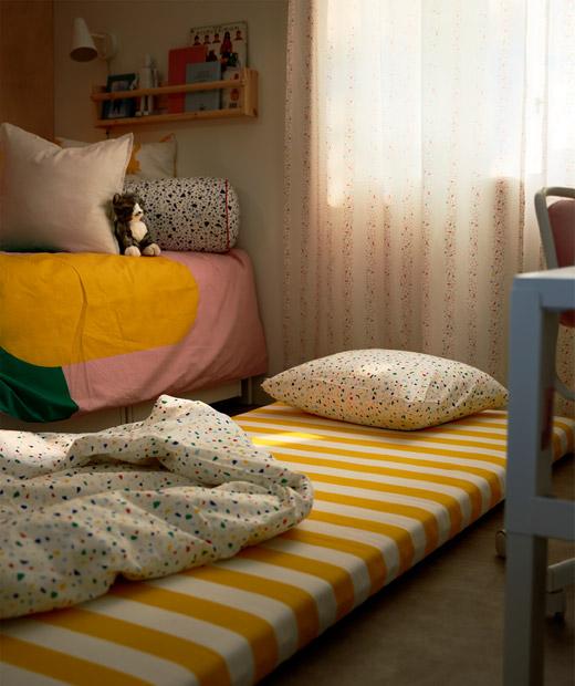 Kasur dengan bantal dan selimut diletakkan di lantai di samping tempat tidur anak. Lampu redup dan tirai kamar tertutup.