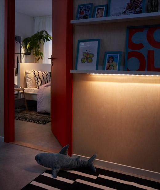 Koridor atau ruang di luar kamar tidur di mana lampu strip LED menerangi lantai secara lembut dari bagian bawah ambalan rak.