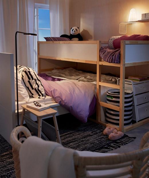 interior kamar dengan tempat tidur tingkat bersebelahan dengan tempat tidur lebih rendah, sebagai ranjang anak yang berada di atas tempat tidur orang tua.