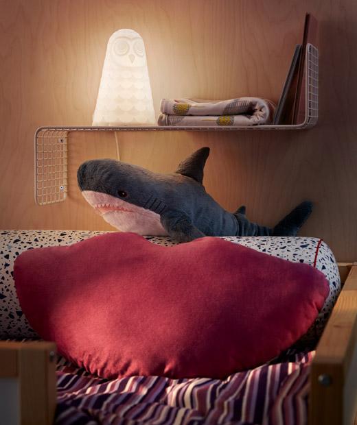 Ujung bantal di tempat tidur tingkat dengan bantal duduk, boneka hiu dan rak dinding untuk meletakkan lampu tidur, buku, quilt.