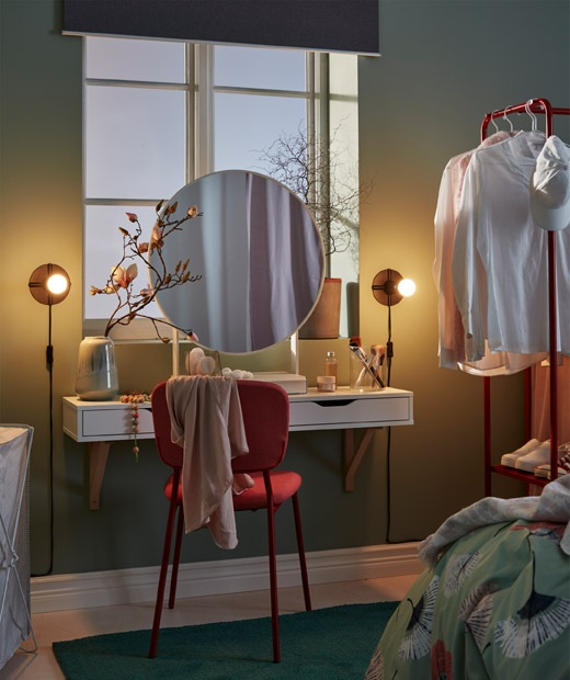 Make-up spot, under a bedroom window, with a round mirror, a wall shelf with drawers as a small worktop, chair and lighting.