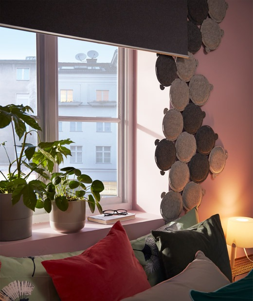 Bed by a window equipped with a black-out roller blind and framed by multiple small, round sound-absorbing panels.