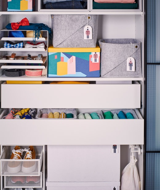 Doorless wardrobe frame filled with various drawers and boxes, in turn filled with clothes and accessories.