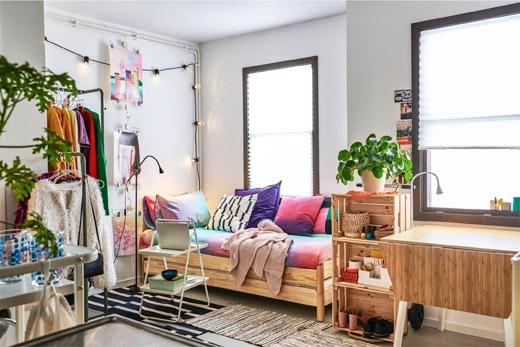 Apartemen kecil penuh barang yang diisi rak, lemari pakaian dan sofa yang terbuat dari bantal dan dua tempat tidur tumpuk.