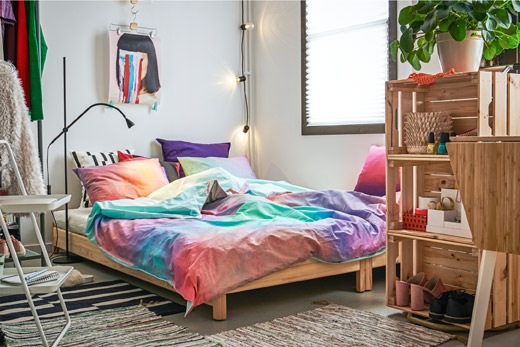 Corner of a room with a made, low double bed surrounded by an apple-crate bookcase and a clothes rack.