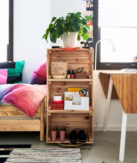 Sebuah rak buku yang terbuat dari peti kayu diletakkan di samping dan ditumpuk. Ditempatkan di antara tempat tidur dan meja makan kecil.