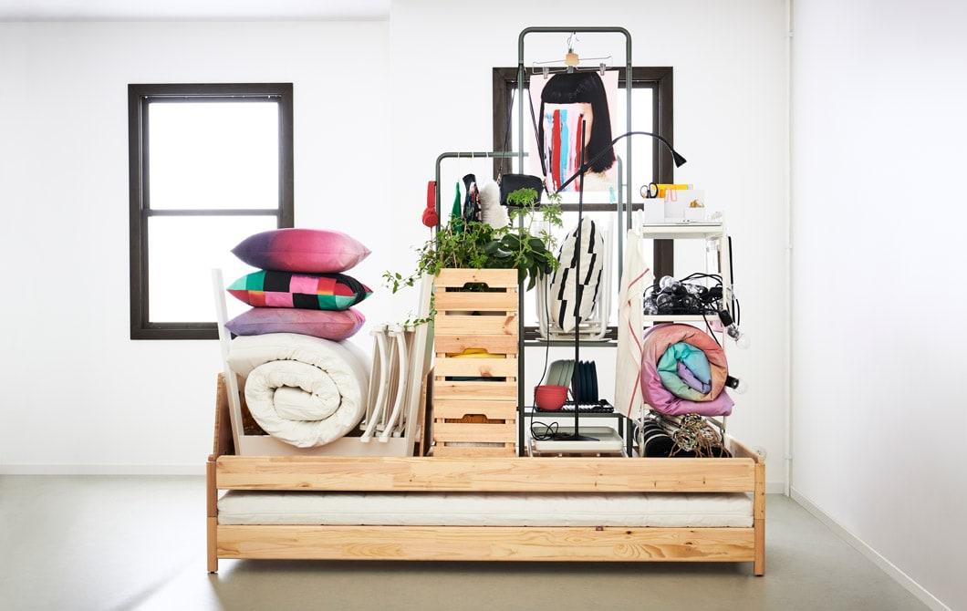 Sebuah interior ruangan atau apartemen dengan dinding polos. Sebuah tempat tidur di tengah ruangan menampung semua perabot dan kebutuhan dari sebuah rumah kecil.