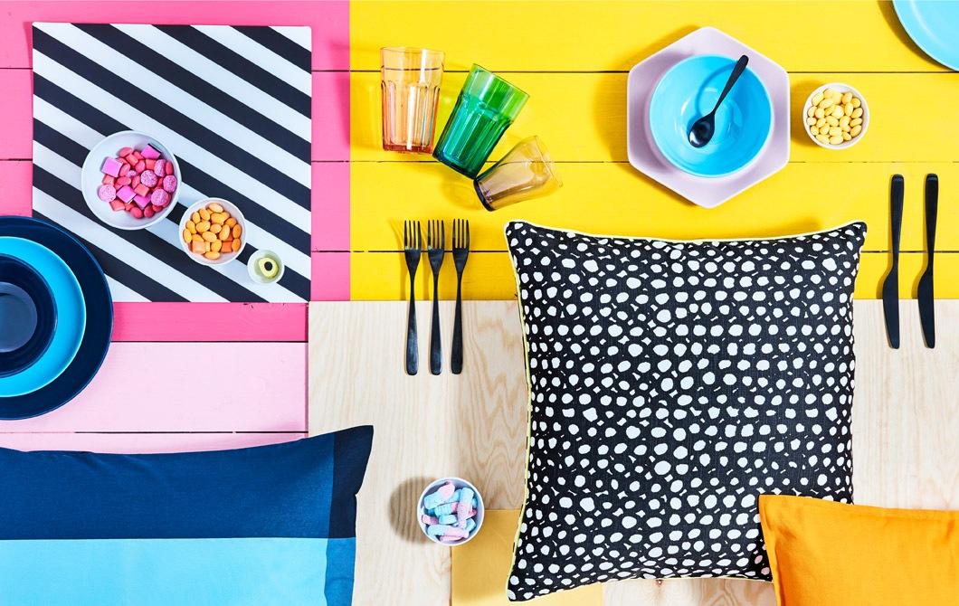 Permukaan berwarna cerah dengan berbagai peralatan makan, mangkuk permen dan bantal bermotif diletakkan di atasnya.