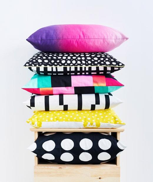 Bantal duduk - hitam dan putih, pola grafis, warna-warna berani yang dipadukan - menumpuk di atas sebuah lemari laci.