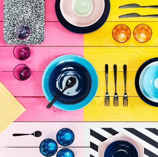 Permukaan berwarna cerah dengan berbagai mangkuk, alat makan dan gelas warna-warni diletakkan di atasnya.