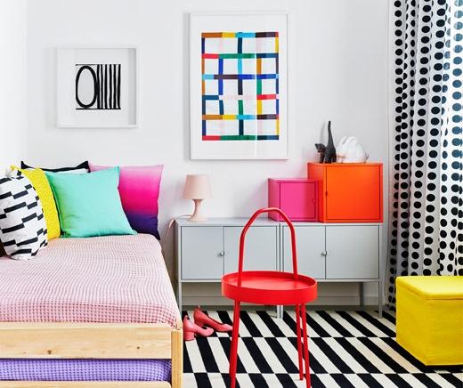Kamar tidur dengan perabot penuh warna dan pola grafis. Tempat tidur dengan bantal, lemari EKET berada di dekatnya.