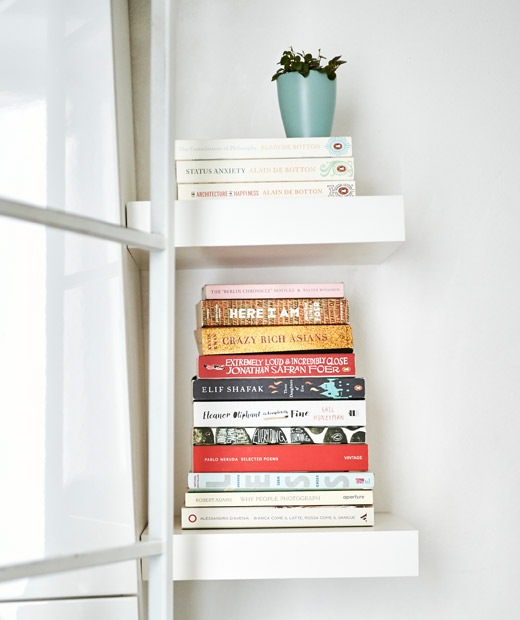 Stacks of books on miniature white shelves.