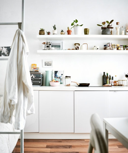 An all-white kitchen with open shelves and a bed ladder in the foreground.