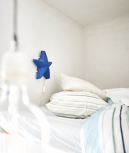 A blue star-shaped lamp on a wall above a bed with patterned textiles.