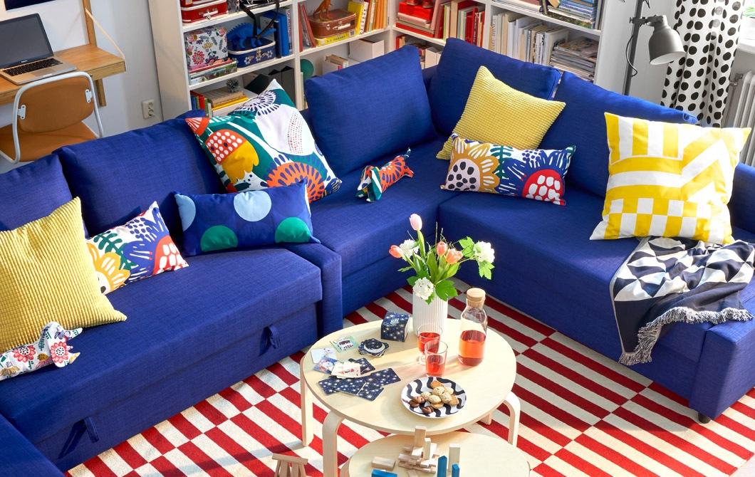 Sofa sudut biru dengan bantal warna-warni, dua meja kopi bundar, dan karpet dengan motif bergaris.