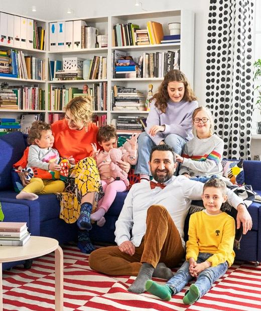 Area duduk ruang keluarga dengan sebuah sofa sudut berwarna biru dilengkapi dengan rak buku di bagian belakang.