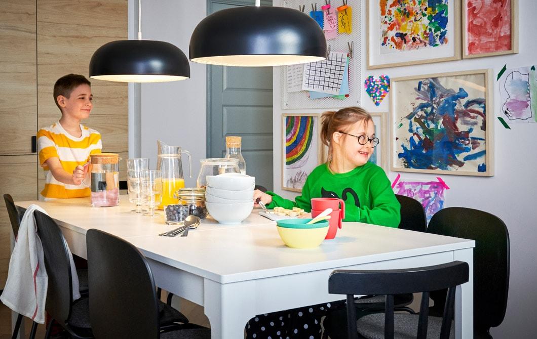 Dua anak duduk di sebuah meja makan berwarna putih yang besar dilengkapi dengan lampu gantung berwarna hitam dan tembok yang dipenuhi hasil karya anak-anak yang terbingkai di bagian belakang.
