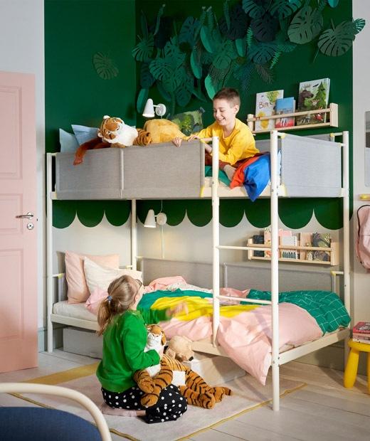 Dua anak berada dalam kamar berwarna hijau - putih dengan tempat tidur tingkat dan rak buku yang dipasang di dinding.