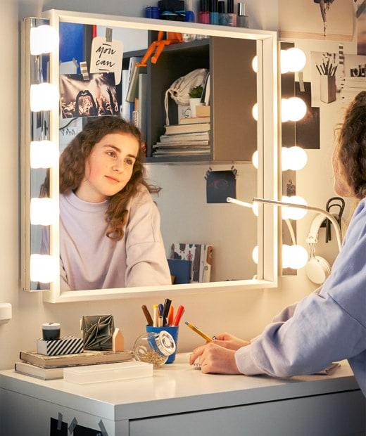 Seorang anak perempuan melihat ke cermin yang dilengkapi dengan pencahayaan dari bagian atas meja berwarna putih.