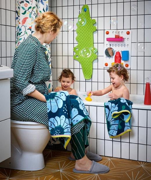 Dua anak berada dalam kamar mandi dengan keramik putih dan seorang wanita duduk di atas toilet disamping mereka.
