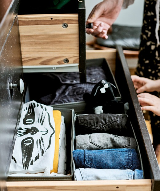 Two open drawers in a chest made of black-stained wood, with t-shirts and jeans neatly folded inside one.