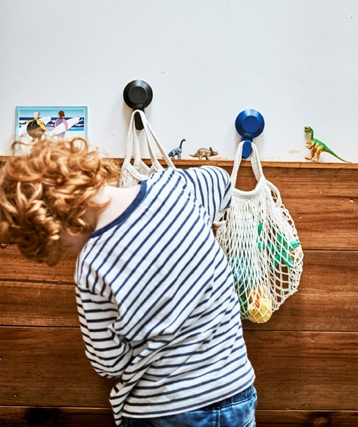 A boy rummages in a string bag of toys hanging from a hook, with another bag and hook on a white wall with wood panelling.