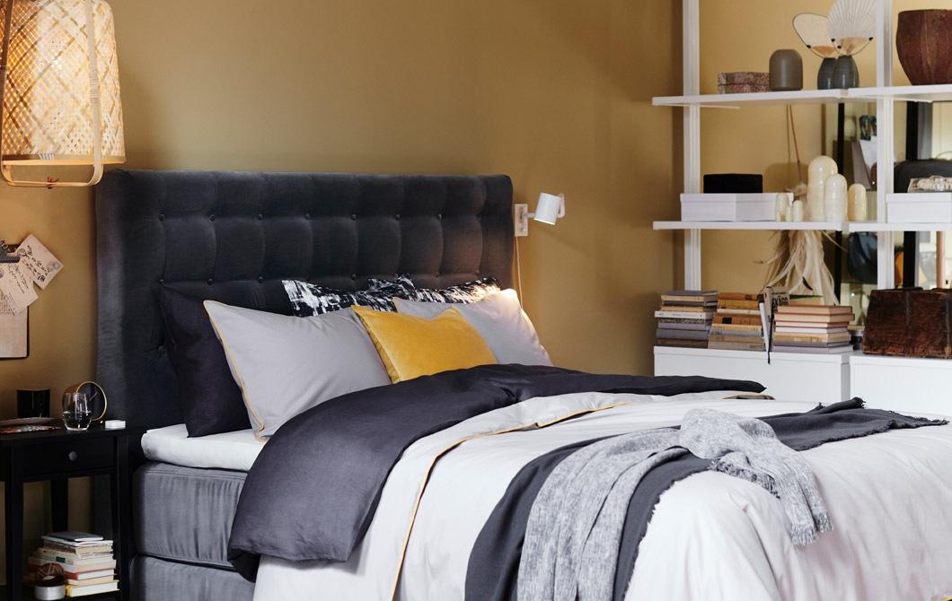 Tempat tidur dengan sandaran kepala tempat tidur berlapis beludru abu-abu dan seprai berlapis.