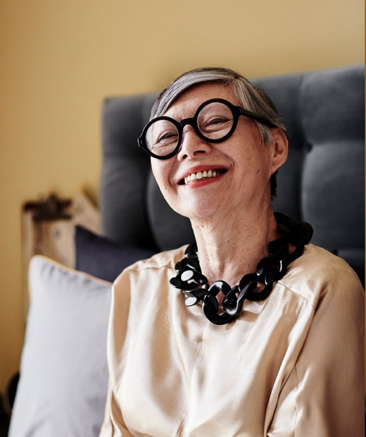 Potret seorang wanita yang mengenakan kacamata dan kalung hitam.