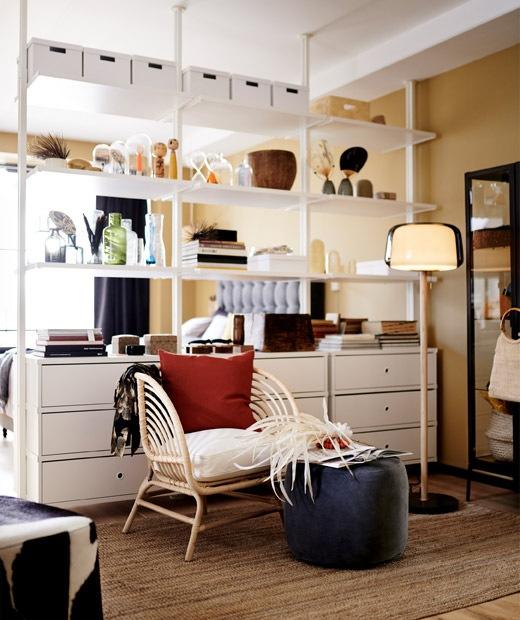 Unit penyimpanan modular putih yang digunakan sebagai pembagi ruang di ruang keluarga tanpa sekat.