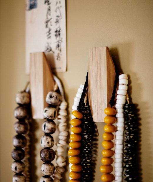 Kalung manik-manik berwarna-warni yang digantung di dua pengait berbahan kayu.
