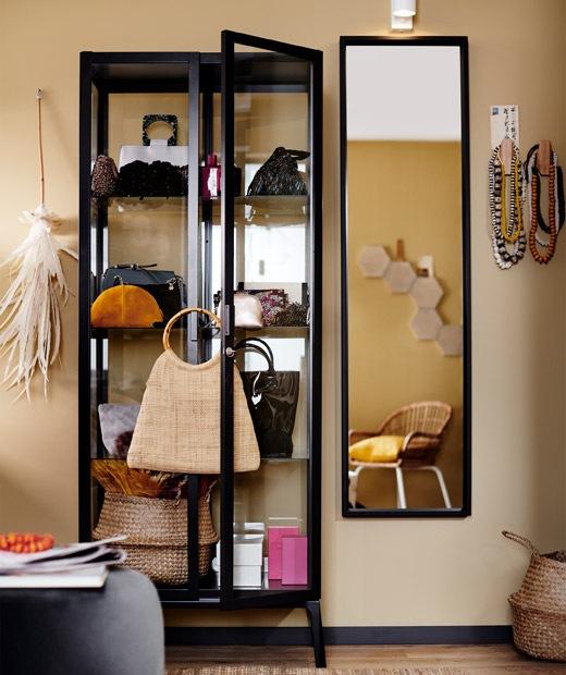 Lemari display kaca berbingkai hitam yang berisi bermacam tas dan aksesoris disebelah cermin.
