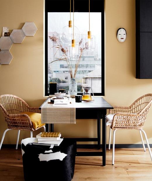 Pengaturan meja makan dengan dua kursi rotan dan sebuah pouffe di depan jendela, ditambah lampu gantung berbahan kaca.
