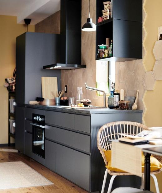 Dapur hitam satu dinding dengan penghisap asap dapur yang ditempel di dinding dalam ruangan dengan cat berwarna kuning lembut.