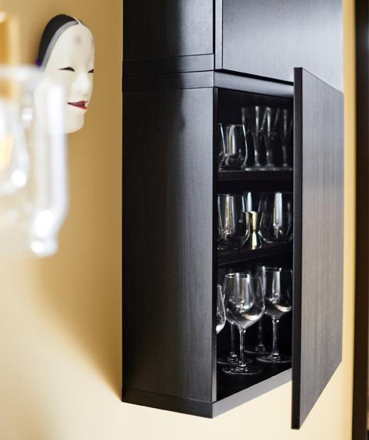 lemari hitam yang dipasang di dinding dengan pintu yang dibuka untuk memperlihatkan barang pecah belah yang diletakkan di dalamnya.