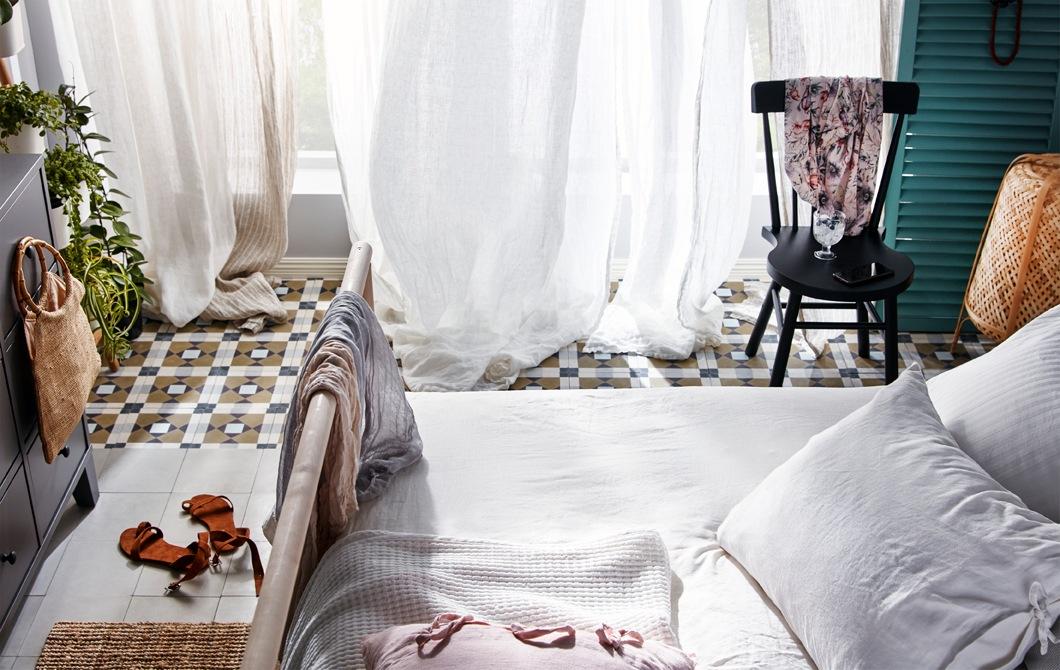 Tempat tidur dengan jendela terbuka dengan gorden terpasang, terlihat mengayun sesuai arah angin yang berhembus masuk.