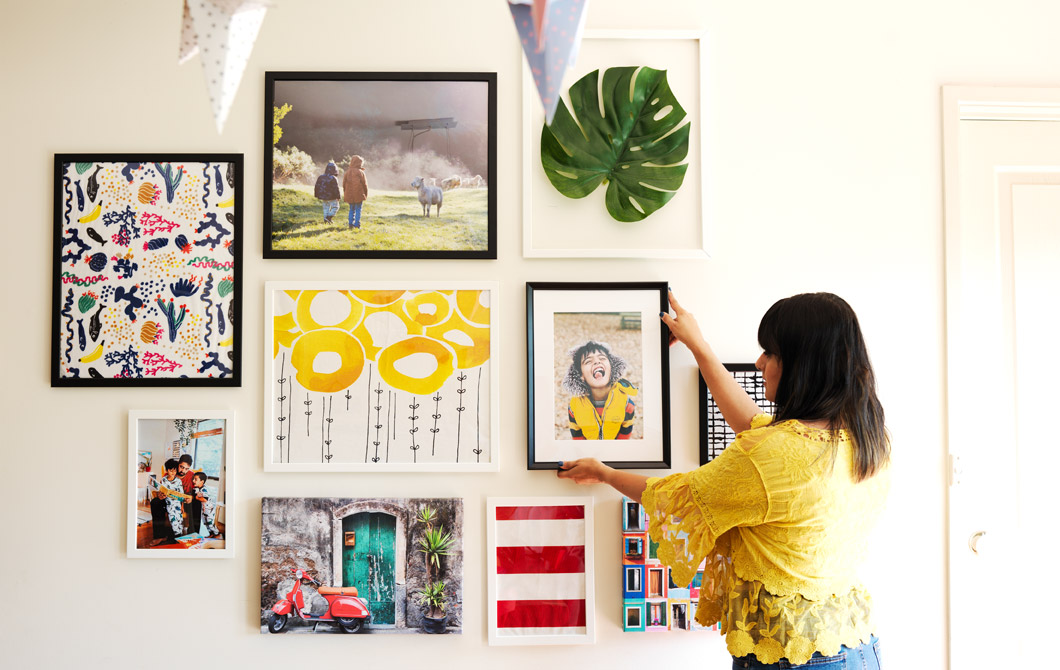 Abeer placing a framed photograph on a gallery wall of pictures and artwork.