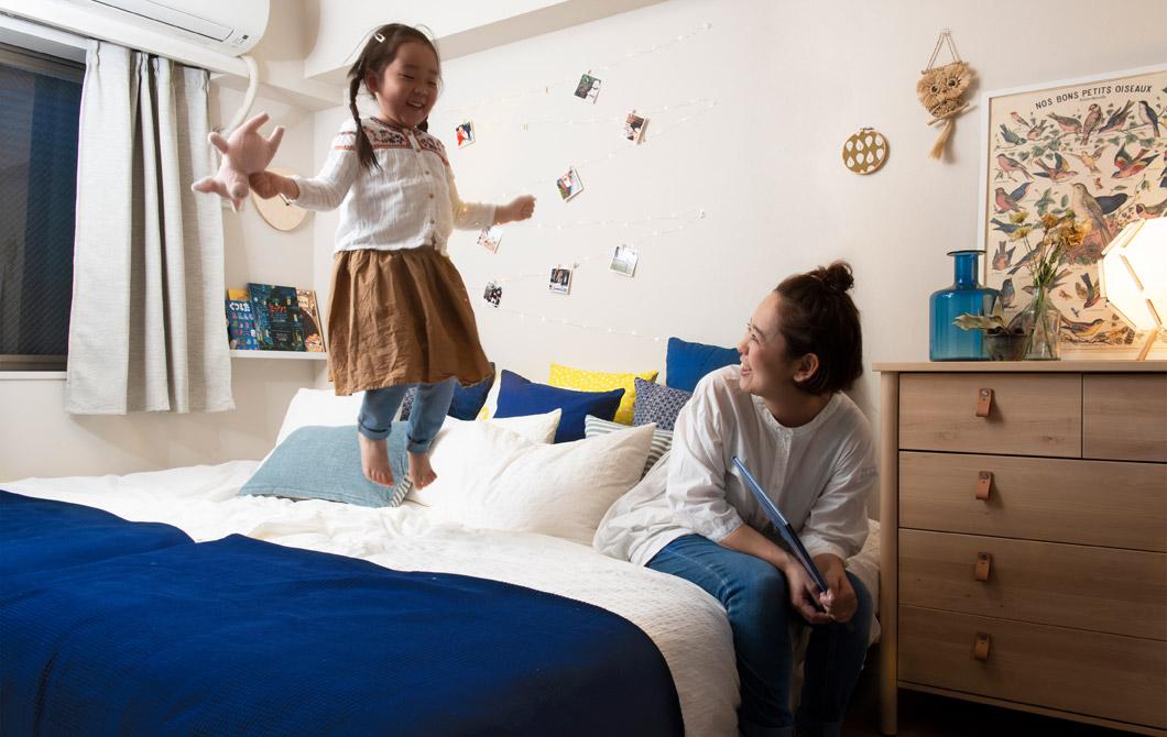 Seorang wanita duduk dan seorang anak berdiri di sebuah tempat tidur besar di kamar tidur putih dengan rak buku yang terpasang di dinding.