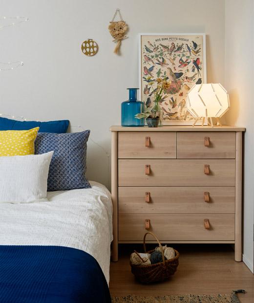 Sudut tempat tidur dengan perlengkapan tidur berwarna biru dan putih di sebelah laci di kamar tidur berwarna putih.