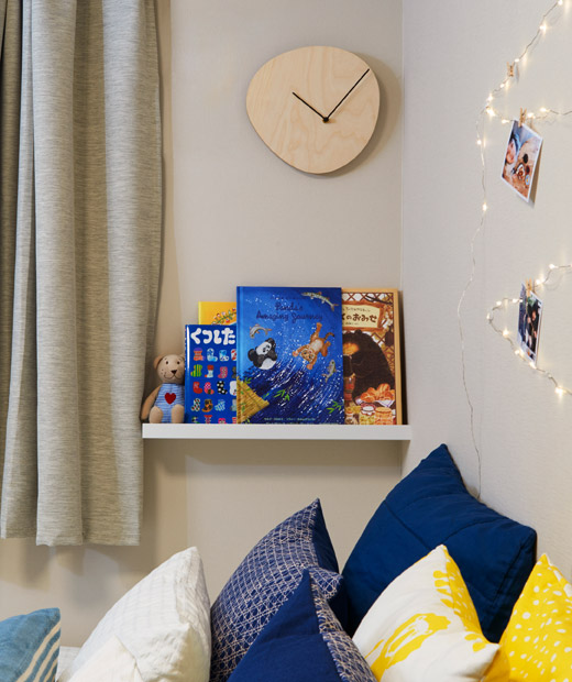 Jam dinding kayu dengan tampilan sederhana dan rak buku yang penuh dengan buku anak-anak di atas tempat tidur yang penuh bantal.